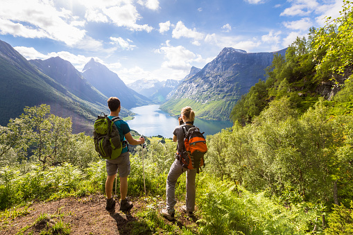istock Two hikers at viewpoint  in mountains with lake, sunny summer 814397912