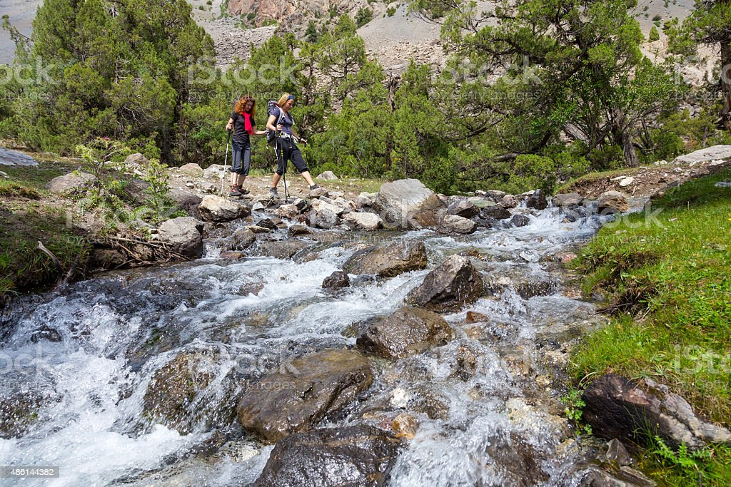 Two hikers crossing fast flowing river stock photo