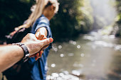 Two hikers in nature. Closeup of man and woman holding hands while crossing the creek. Focus  on hands of couple.