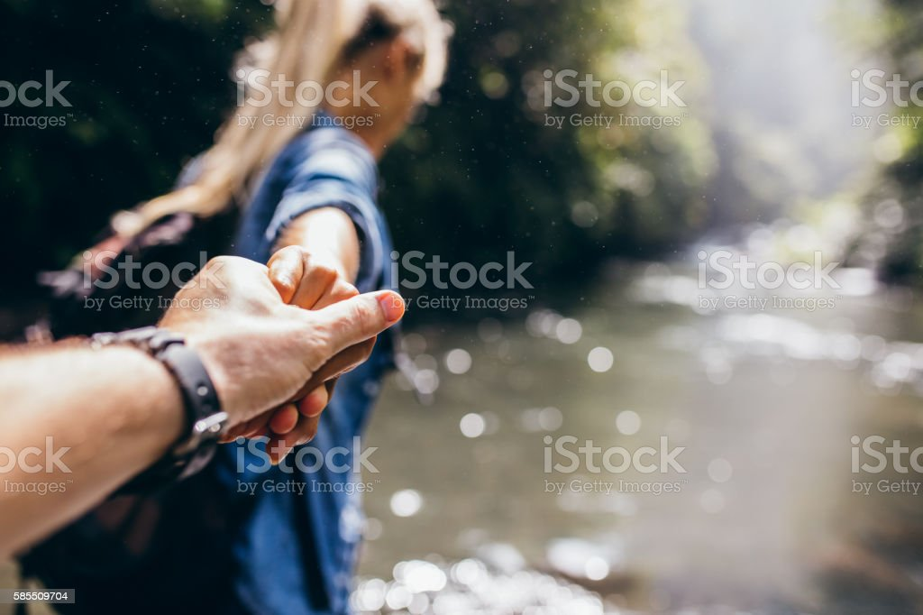 Two hikers in nature crossing the stream holding hands stock photo