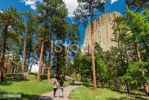 Two hikers are hiking on a trail around Devil Towers, Wyoming, United States. They stop to admire the beautiful forest and the mountain.
