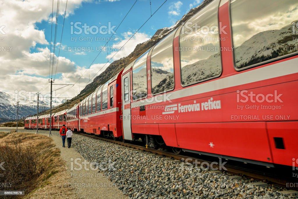 Two hikers near famous Bernina Express train near Pontresina, Switzerland stock photo