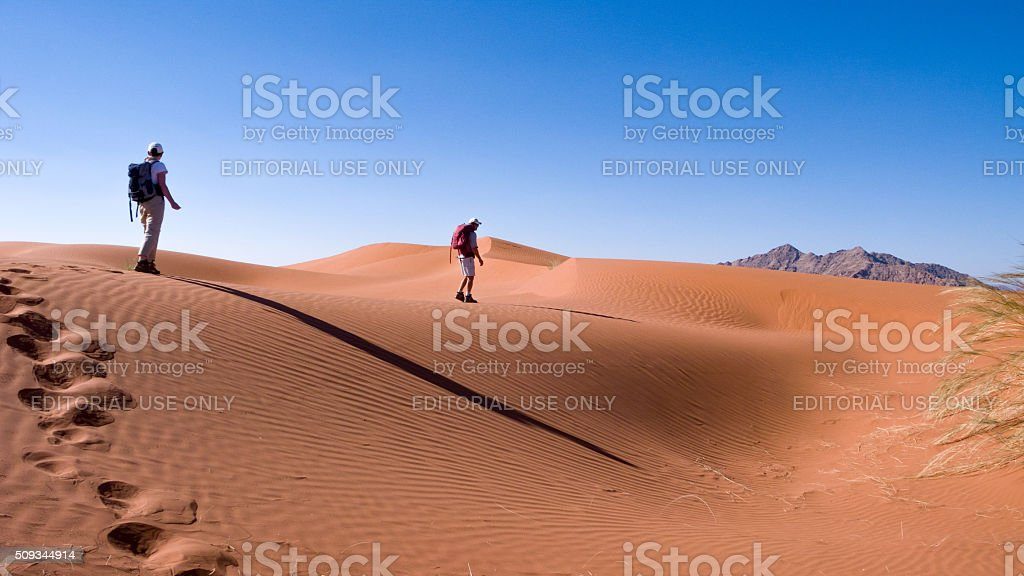 Two Hikers on top of a sand dune in Namibia stock photo