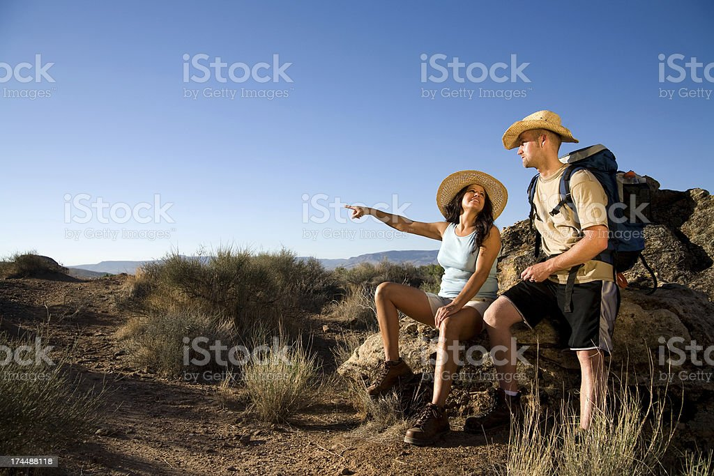 Two hikers sitting on rock under blue sky stock photo