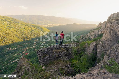 Young Caucasian man and woman standing on the edge of a cliff looking at the valley.
