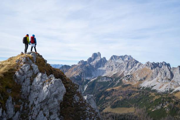 Zwei Wanderer stehen hoch oben mit herrlichem Ausblick – Foto