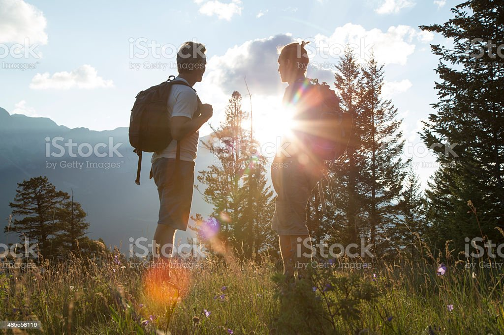 Two hikers watch sunrise from mountain meadow stock photo