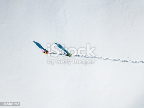 istock Two hikers with long shadows walking over snow (aerial shot) 938304948