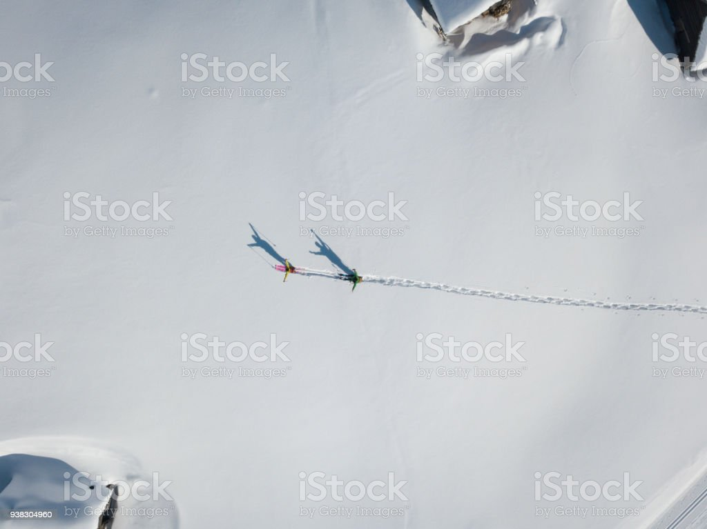 Two hikers with raised arms in deep snow from above stock photo