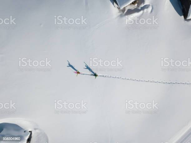 Photo of Two hikers with raised arms in deep snow from above
