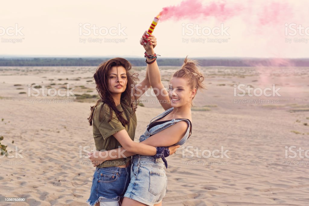 Two hipster girls having fun on the desert, holding distress flare Two young women having fun on the dune, holding distress flare in hand. Adolescence Stock Photo