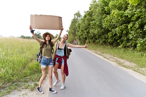 Two Hipster Girls Hitchhiking Together Stock Photo - Download Image Now