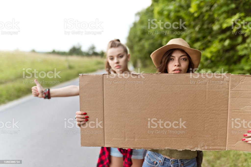 Two hipster girls hitchhiking together Outdoor shot of two young women standing on the road and hitchhiking. 20-24 Years Stock Photo