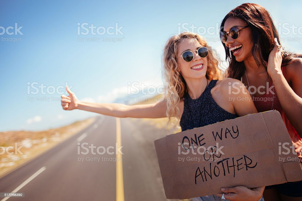Two Hipster Girls Hitchhiking Together stock photo