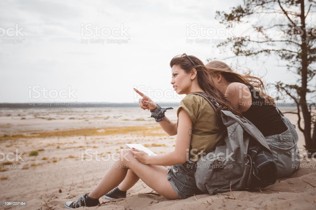 Two hipster girls sitting on the desert Outdoor shot of two young women sitting on the dune, holding backpacks. Adolescence Stock Photo