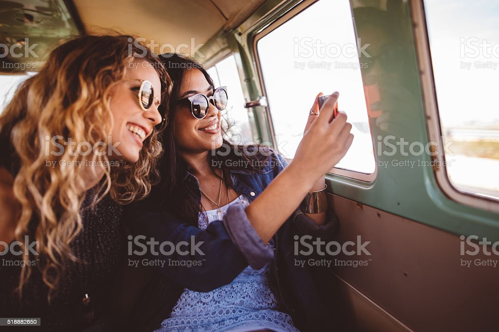 Two Hipster Girls Sitting Together taking a road trip photo stock photo