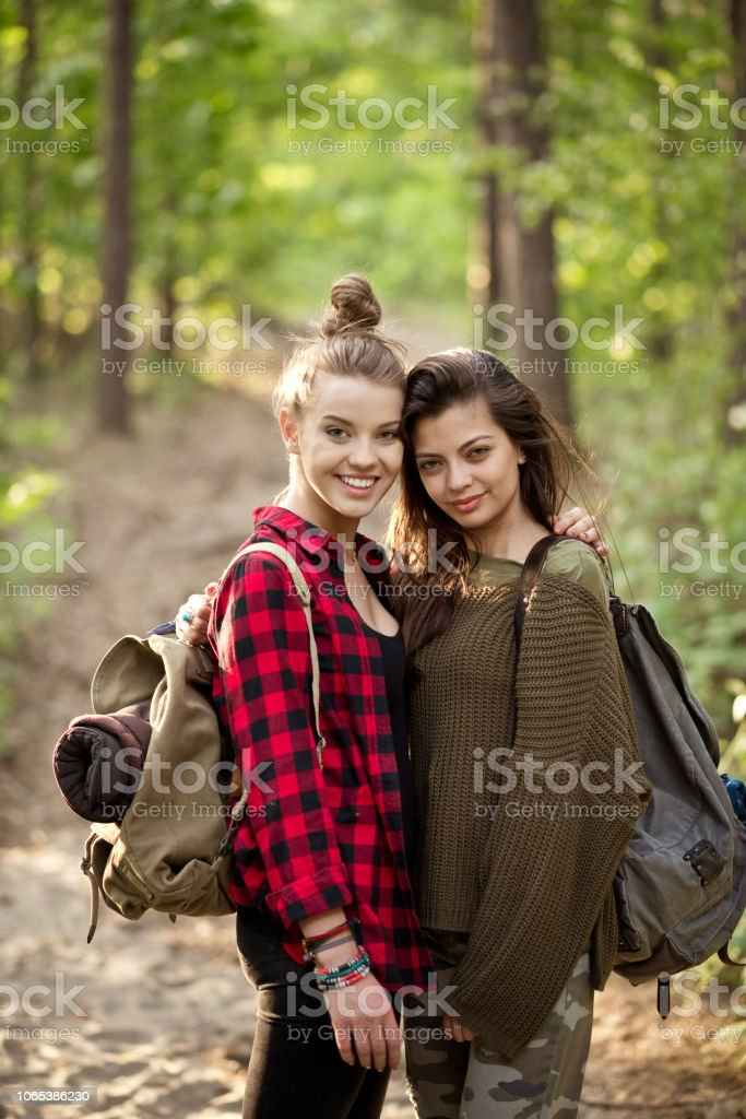 Two hipster girls standing in the forest Outdoor shot of two young women embracing in the forest, holding backpacks, smiling at camera. Adolescence Stock Photo