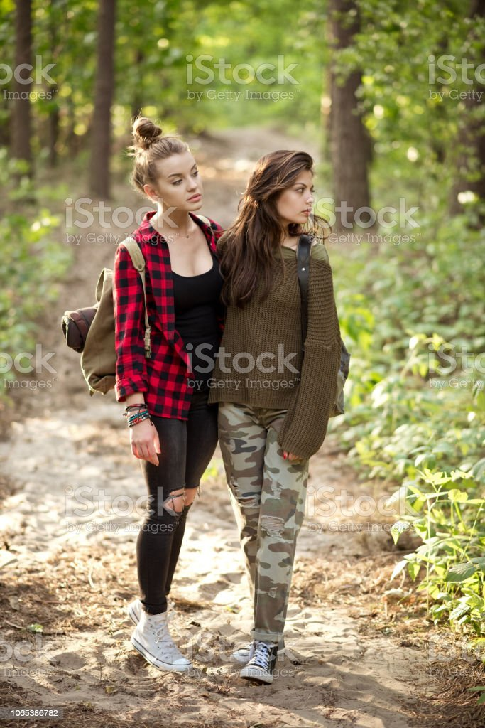 Two hipster girls standing in the forest Outdoor shot of two young women embracing in the forest, holding backpacks, looking away. Adolescence Stock Photo
