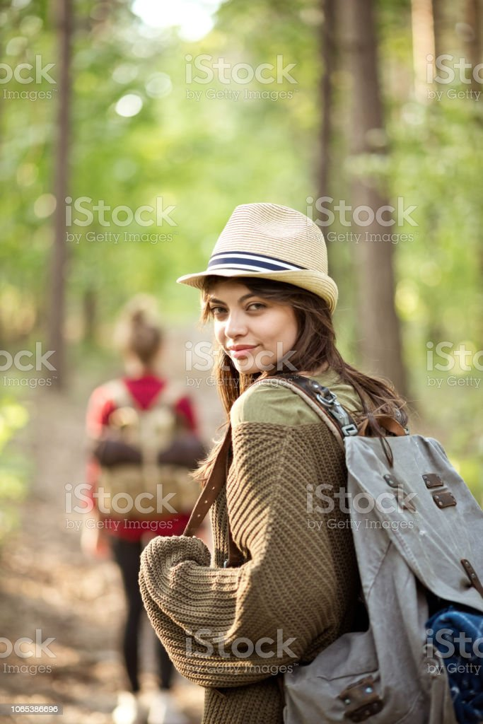 Two hipster girls walking in the forest Outdoor shot of two young women walking in the forest. Brunette smiling at the camera. Adolescence Stock Photo
