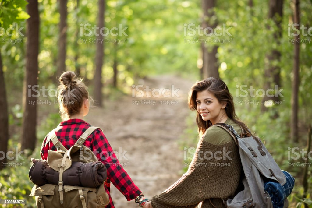 Two hipster girls walking in the forest Outdoor shot of two young women walking in the forest, holding hands. Brunette smiling at the camera. Adolescence Stock Photo