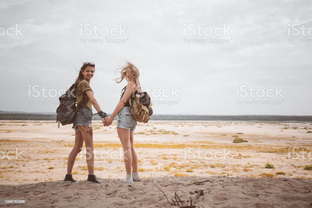 Two hipster girls walking on the desert, holding backpackes Outdoor shot of two young women walking on the dune, holding hands. Adolescence Stock Photo