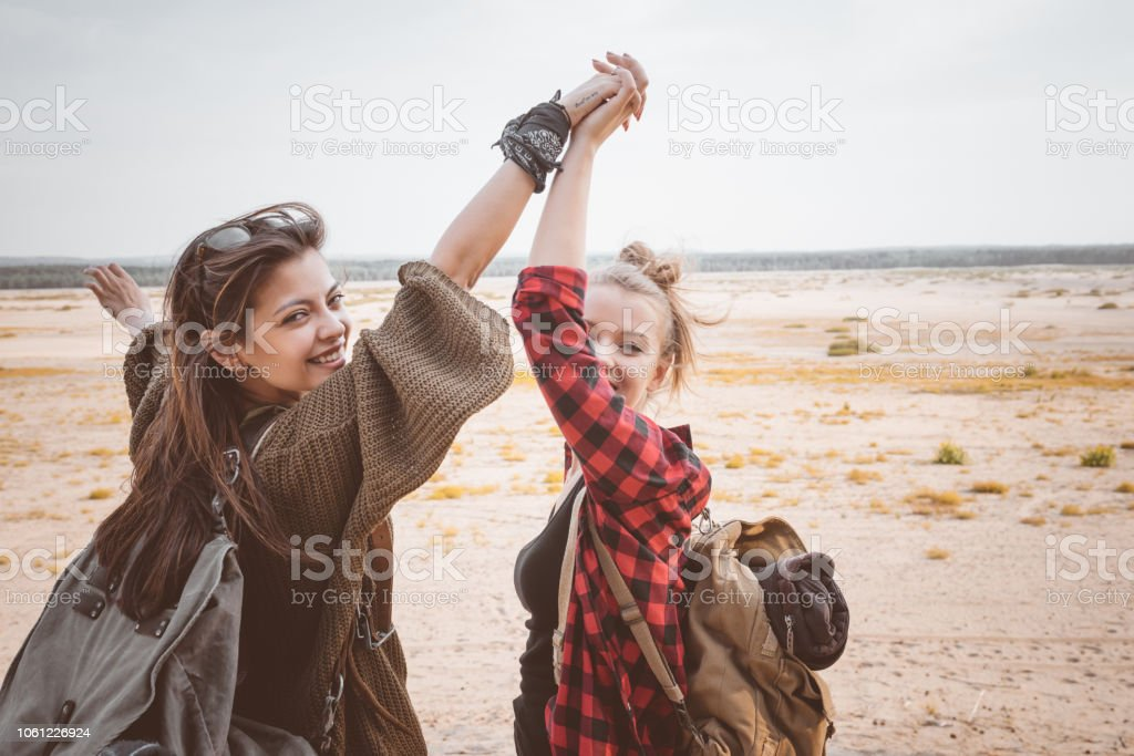 Two hipster girls walking on the desert, holding backpackes Outdoor shot of two  happy young women walking on the dune, holding hands, smiling at camera. Adolescence Stock Photo