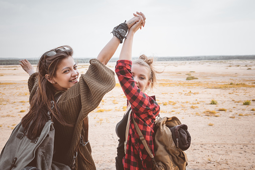 Two Hipster Girls Walking On The Desert Holding Backpackes Stock Photo - Download Image Now