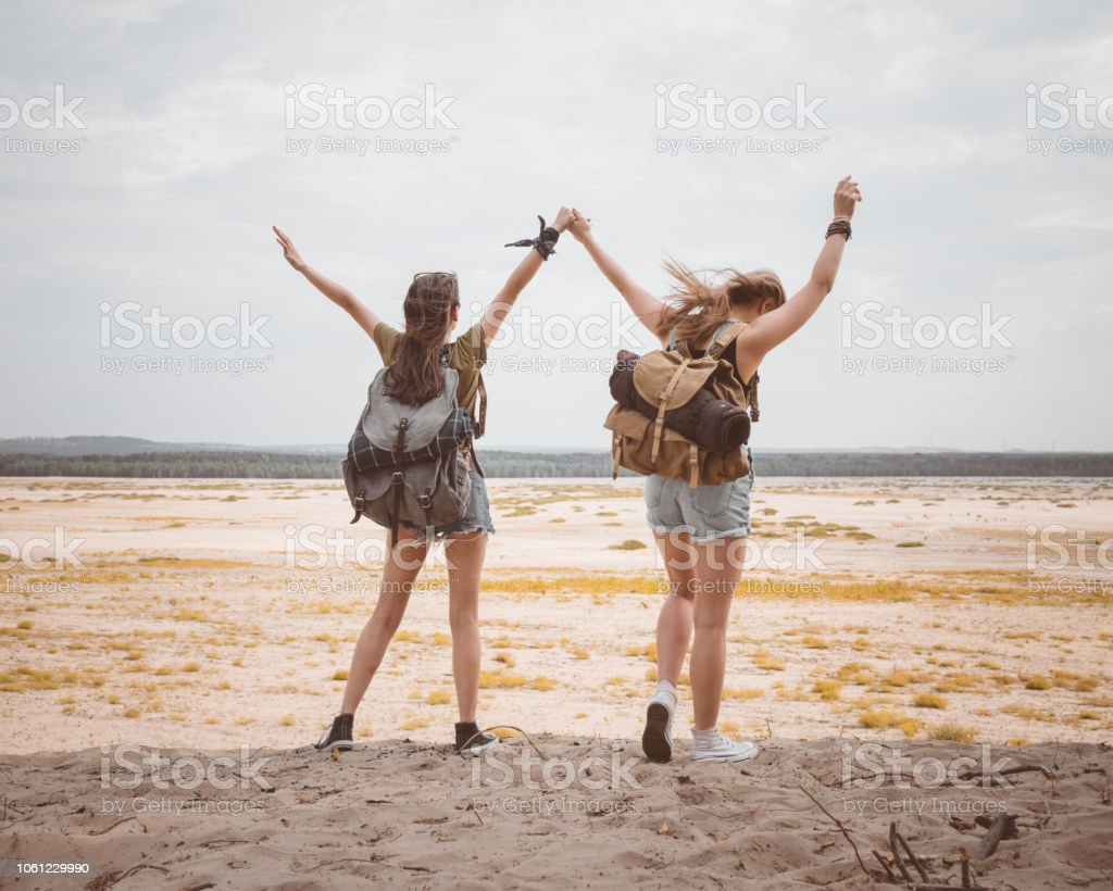 Two hipster girls walking on the desert, holding backpackes Outdoor shot of two excited young women walking on the dune, holding hands. Back view. Adolescence Stock Photo
