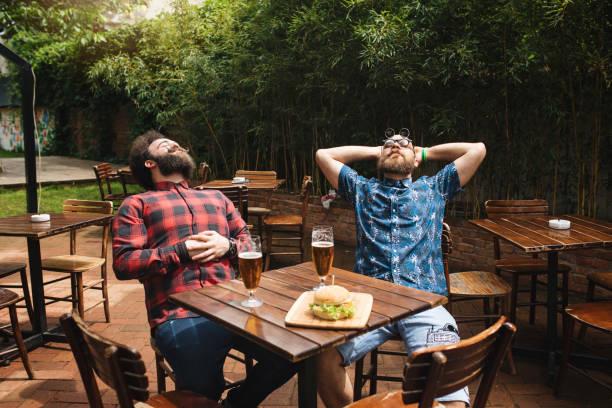 zwei hipster-männer zufrieden mit ihrem mittagessen - bier gesund stock-fotos und bilder