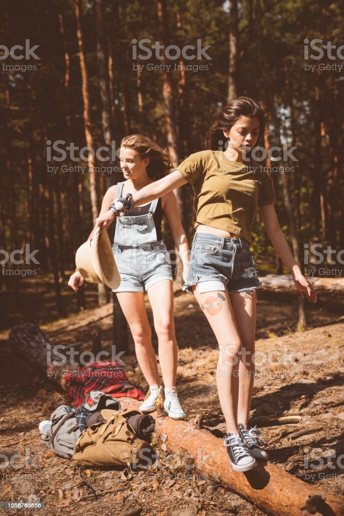 Two hipter girls playing in the forest Outdoor shot of two young women walking on the fallen tree in the forest. Adolescence Stock Photo