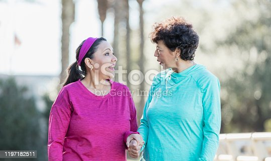 Two Hispanic women talking and walking together in the park, best friends holding hands. They are wearing casual clothing, sweatshirts. The one in blue is a senior woman in her 60s. Her friend is a mature woman in her 50s.