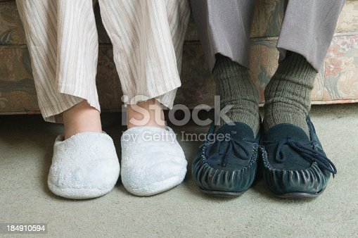 istock Two home slippers worn by people sitting on the couch 184910594