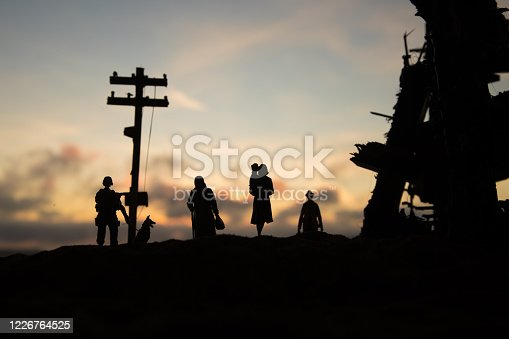 Refugees and captive walking in destroyed city. Terrible face of war concept. Creative artwork table decoration with light and fog. Selective focus.
