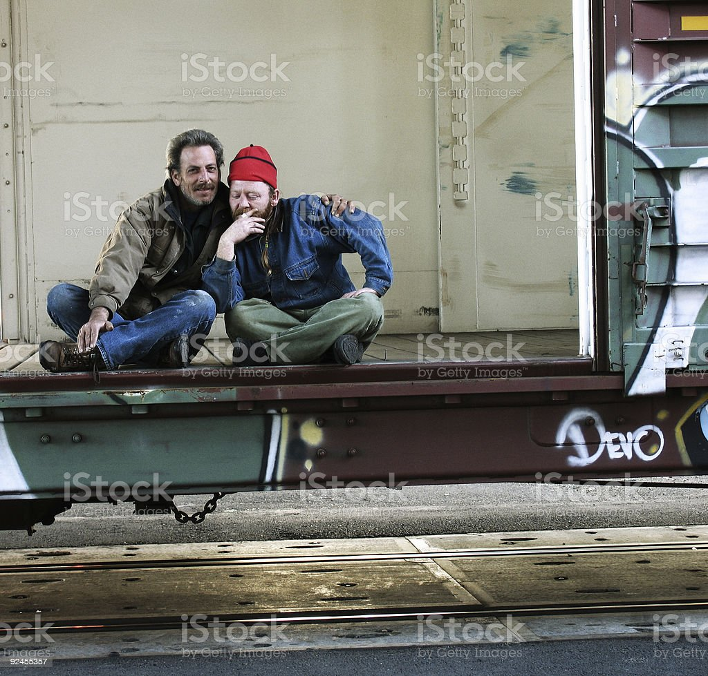 Two Homeless Men Sitting in Old Train Car stock photo