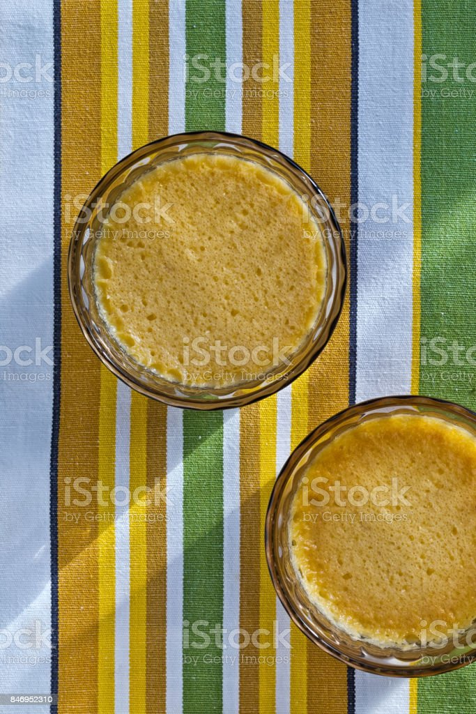 Two Homemade Crème Brûlée on a stripy green, stock photo