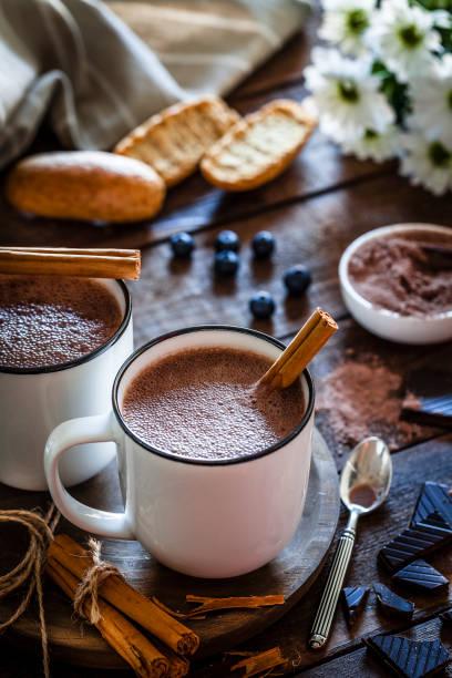 zwei hausgemachte heiße schokolade becher auf rustikalen holztisch - kaffee protein shakes stock-fotos und bilder
