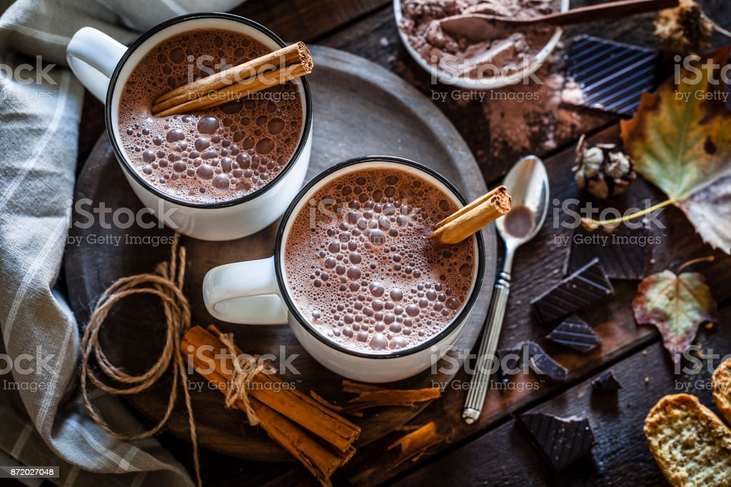 Two homemade hot chocolate mugs on rustic wooden table stock photo