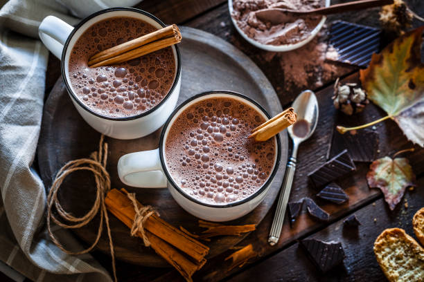 two homemade hot chocolate mugs on rustic wooden table - hot chocolate stock photos and pictures