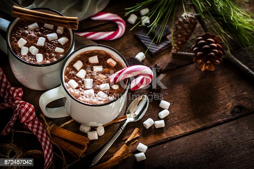 High angle view of two homemade hot chocolate mugs with marshmallows shot on rustic wooden Christmas table. A candy cane is inside one mug and another is placed directly on the table. Christmas decoration complete the composition. Low key DSRL studio photo taken with Canon EOS 5D Mk II and Canon EF 100mm f/2.8L Macro IS USM