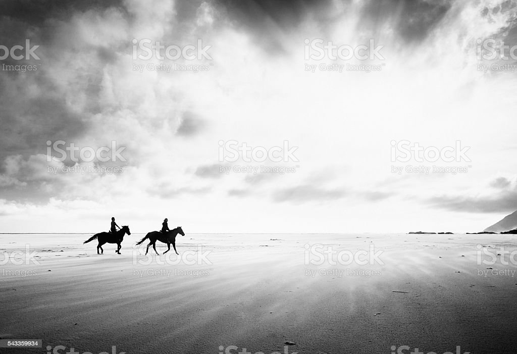 Two horse riders crossing endless stark stretch of sand. Monochrome. stock photo