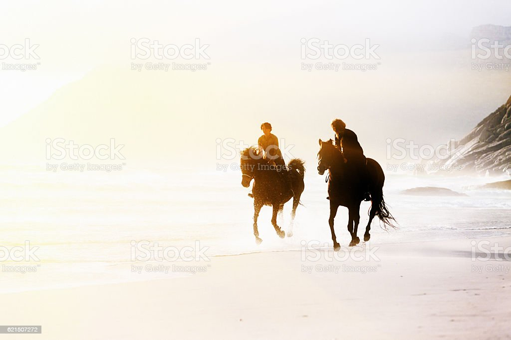 Two horseback riders galloping on wild, windswept beach foto stock royalty-free