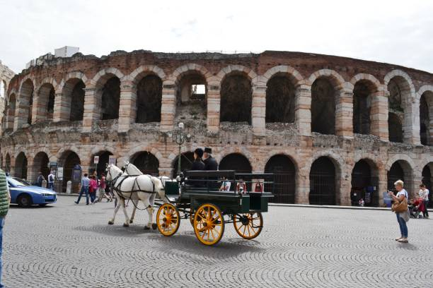 Two horses carriage moving in Piazza Bra along Arena di Verona. stock photo