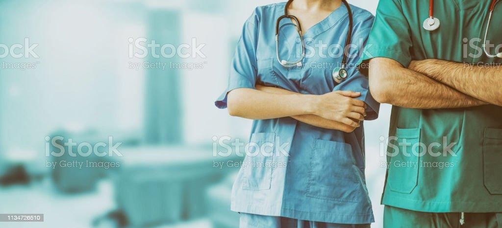 Dos personal hospitalario-cirujano, médico o enfermero de pie con los brazos cruzados en el hospital. Atención médica y servicio médico. - Foto de stock de Alegre libre de derechos