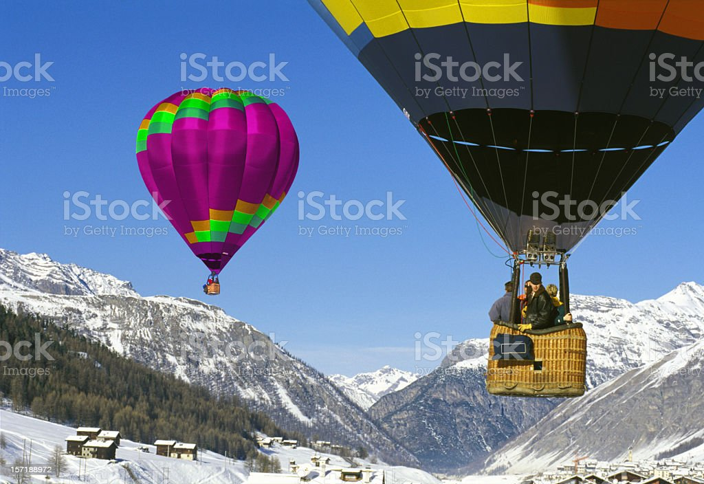 Two hot air balloons flying above winter mountains royalty-free stock photo