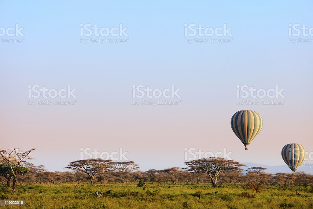 Two hot air balloons over a plains landscape at dusk stock photo