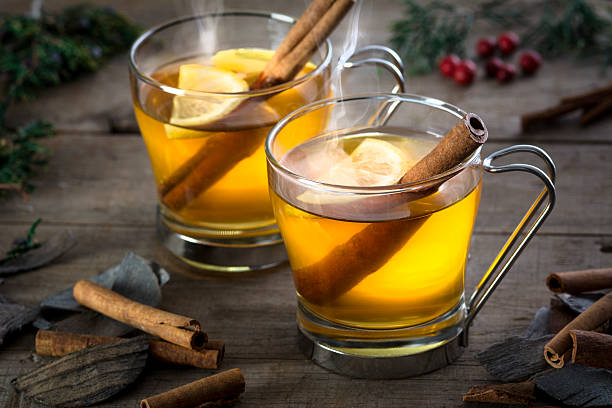 Two Hot Toddy Cocktail Drinks with Cinnamon and Lemmon Two hot  whisky, rum, apple or brandy toddy cocktail drinks with cinnamon set on rustic wood hot apple cider stock pictures, royalty-free photos & images