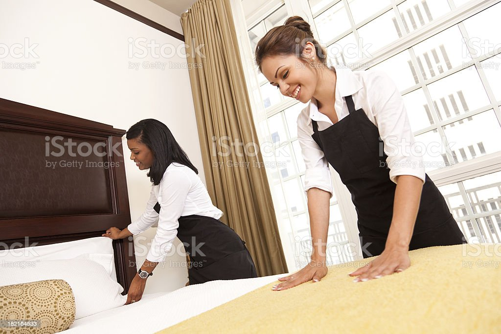 Two hotel maids making up guest room royalty-free stock photo