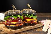 Two huge black hamburgers on dark wooden background. Fast food concept