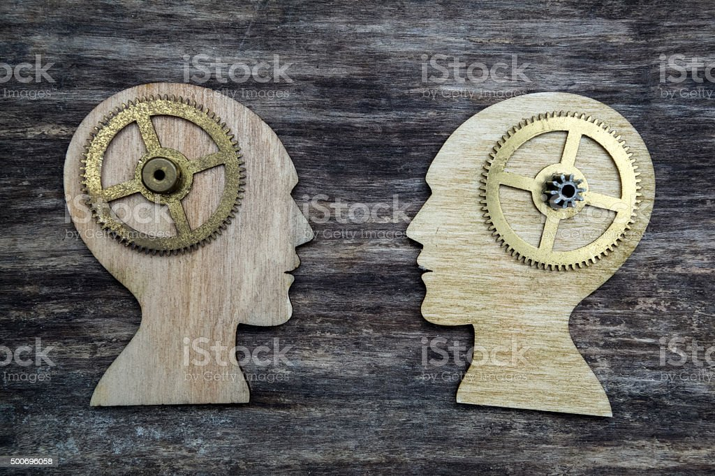 Two human head silhouettes with gears stock photo