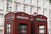 Low angle view of two iconic British red telephone boxes against white buildings, selective focus.
